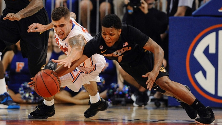 Missouri guard Wes Clark, right, dives for a loose ball with Florida guard Scottie Wilbekin during the second half of an NCAA college basketball game Tuesday, Feb. 4, 2014, in Gainesville, Fla. Florida defeated Missouri 68-58. (AP Photo/Phil Sandlin)