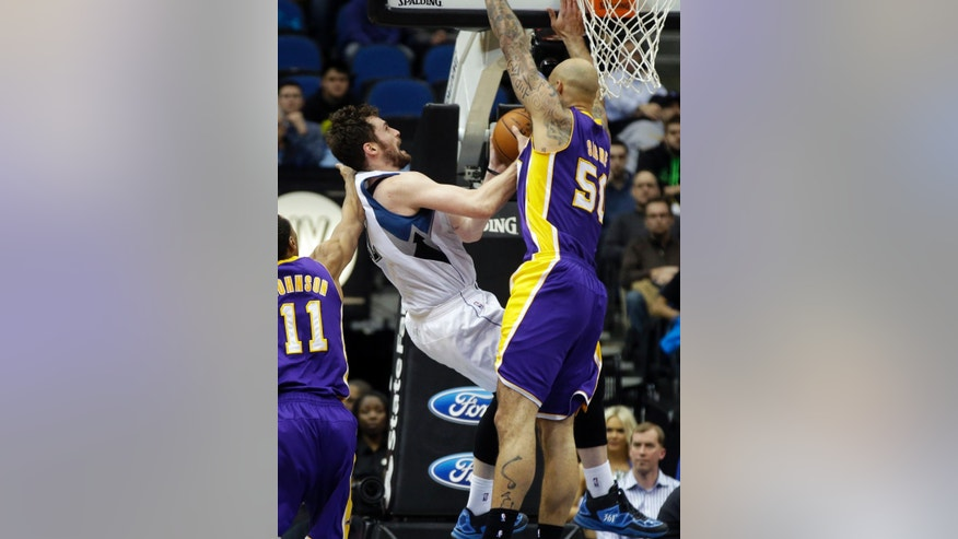 Minnesota Timberwolves' Kevin Love, center, is fouled by Los Angeles Lakers' Robert Sacre, right, during the second half of an NBA basketball game, Tuesday, Feb. 4, 2014, in Minneapolis. The Timberwolves won 109-99. Love, who led his team with 31 points and 17 rebounds, fell to the floor and was attended to but continued in the game. (AP Photo/Jim Mone)