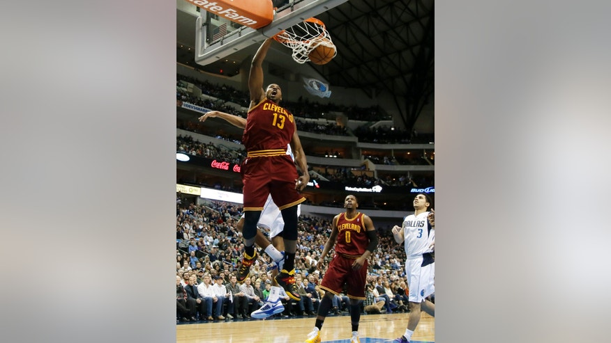 Cleveland Cavaliers' Tristan Thompson (13) dunks after getting past Dallas Mavericks' Brandan Wright, rear, as C.J. Miles (0) and Shane Larkin (3) watch in the first half of an NBA basketball game, Monday, Feb. 3, 2014, in Dallas. (AP Photo/Tony Gutierrez)