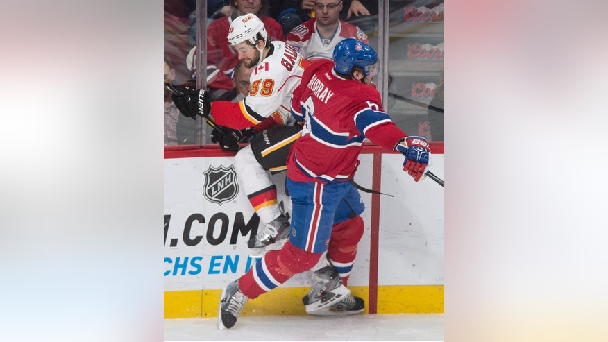 Montreal Canadiens' Douglas Murray, right, collides with Calgary Flames' TJ Galiardi during the second period of an NHL hockey game Tuesday, Feb. 4, 2014, in Montreal. (AP Photo/The Canadian Press, Graham Hughes)