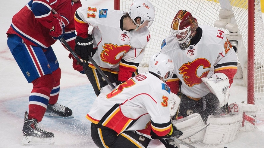 Montreal Canadiens' Rene Bourque, left, scores against Calgary Flames goaltender Reto Berra, right, as Flames' Mikael Backlund (11) and Ladislav Smid defend during the second period of an NHL hockey game Tuesday, Feb. 4, 2014, in Montreal. (AP Photo/The Canadian Press, Graham Hughes)