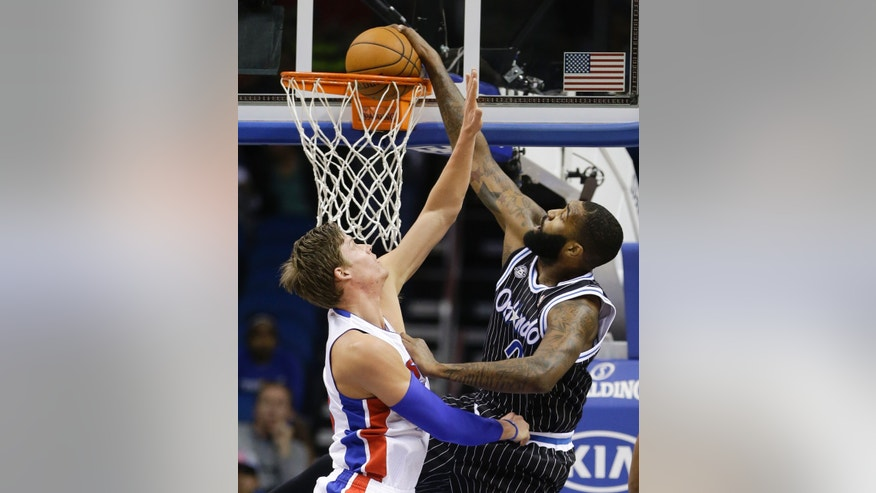 Orlando Magic's Kyle O'Quinn, right, dunks as he gets past Detroit Pistons' Jonas Jerebko during the first half of an NBA basketball game in Orlando, Fla., Wednesday, Feb. 5, 2014. (AP Photo/John Raoux)