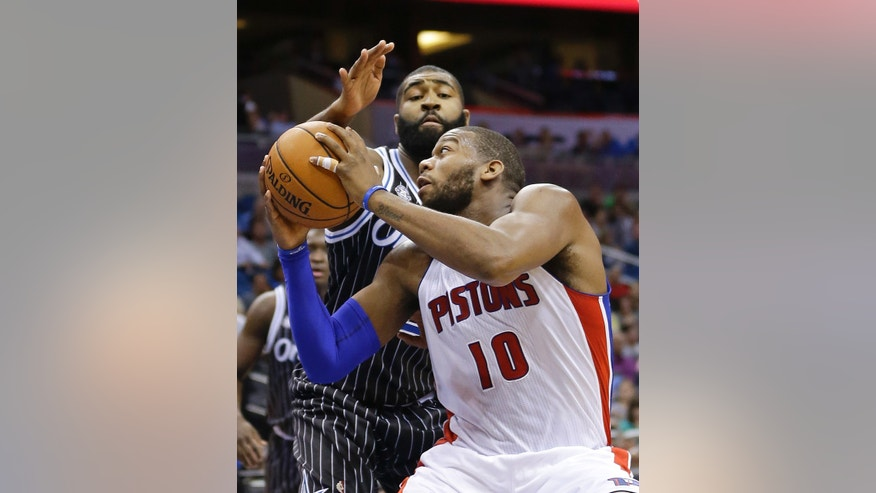 Detroit Pistons' Greg Monroe (10) looks for an open shot as he is guarded by Orlando Magic's Kyle O'Quinn during the first half of an NBA basketball game in Orlando, Fla., Wednesday, Feb. 5, 2014. (AP Photo/John Raoux)