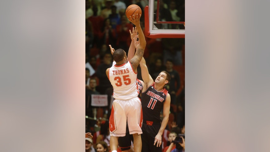 Houston forward TaShawn Thomas (11) takes a shot over Louisville forward Luke Hancock (11) during the first half of an NCAA college basketball game, Wednesday, Feb. 5, 2014, in Houston. (AP Photo/Patric Schneider)