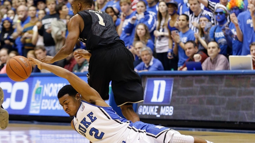 Duke's Quinn Cook (2) falls to the floor as Wake Forest's Madison Jones (1) steals the ball during the first half of an NCAA college basketball game in Durham, N.C., Tuesday, Feb. 4, 2014. (AP Photo/Gerry Broome)