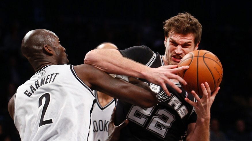 San Antonio Spurs' Tiago Splitter (22), of Brazil, is fouled by Brooklyn Nets' Kevin Garnett (2) during the first half of an NBA basketball game on Thursday, Feb. 6, 2014, in New York. (AP Photo/Jason DeCrow)