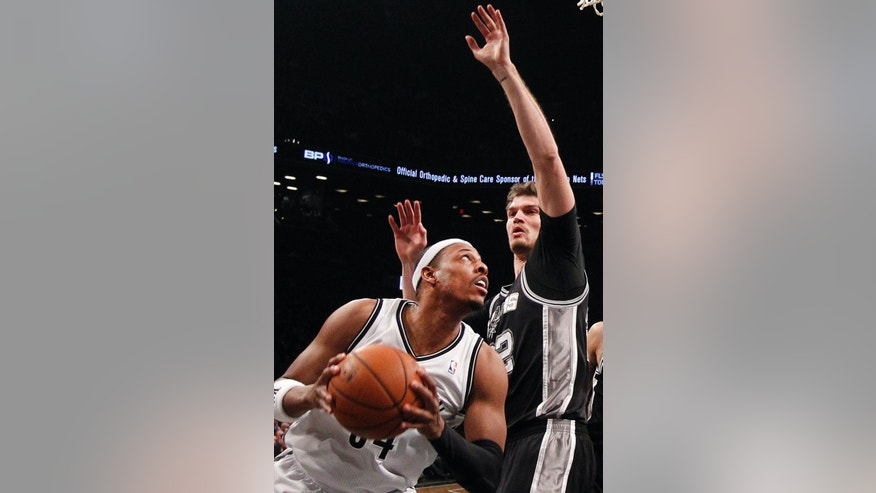 Brooklyn Nets' Paul Pierce, left, looks to shoot against San Antonio Spurs' Tiago Splitter, right, of Brazil, during the first half of an NBA basketball game on Thursday, Feb. 6, 2014, in New York. (AP Photo/Jason DeCrow)