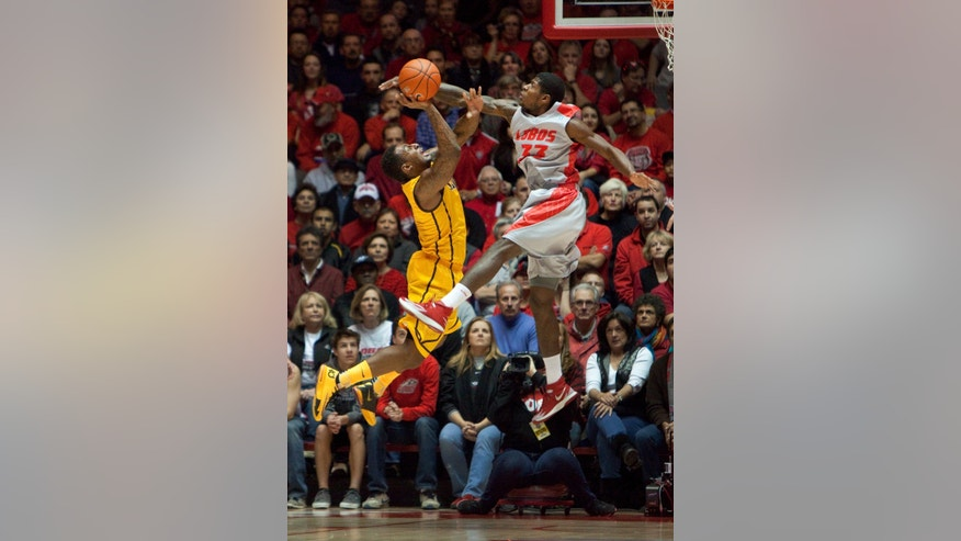 New Mexico's Deshawn Delaney blocks a shot attempt from Wyoming's Charles Hankerson in the first half of an NCAA college basketball game Wednesday, Feb. 5, 2014 in Albuquerque, N.M. (AP Photo/Eric Draper)