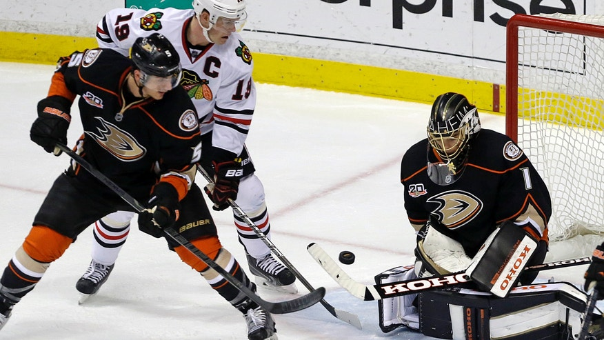 Chicago Blackhawks center Jonathan Toews (19) attacks as Anaheim Ducks goalie Jonas Hiller (1), of Switzerland, and defenseman Luca Sbisa (5), of Italy, defend during the second period of an NHL hockey game in Anaheim, Calif., Wednesday, Feb. 5, 2014. (AP Photo/Reed Saxon)