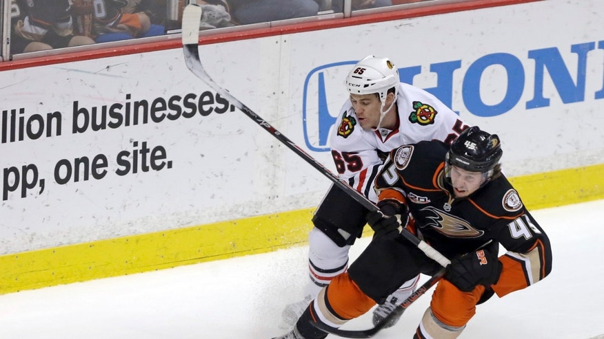Chicago Blackhawks center Andrew Shaw (65) is called for hooking against Anaheim Ducks defenseman Sami Vatanen (45), of Finland, in the first period of an NHL hockey game in Anaheim, Calif., Wednesday, Feb. 5, 2014. (AP Photo/Reed Saxon)