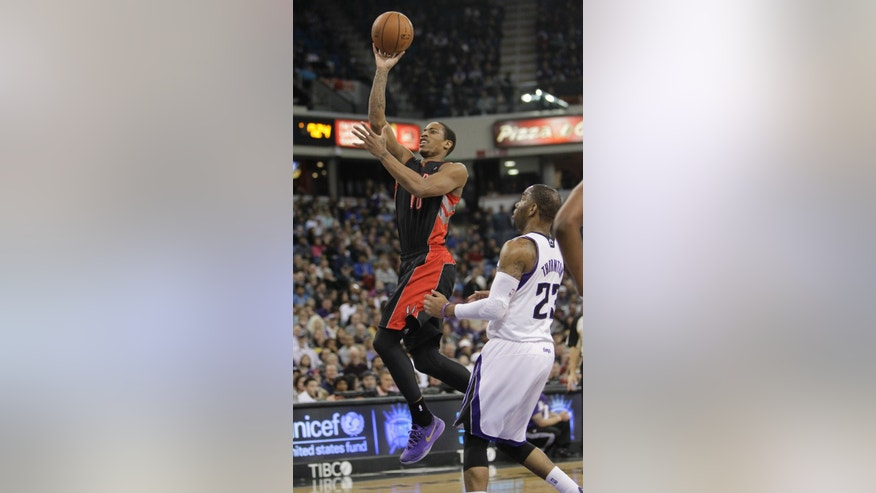 Toronto Raptors guard DeMar DeRozan, right, goes to the basket past Sacramento Kings guard Marcus Thornton during the first quarter of an NBA basketball game in Sacramento, Calif., Wednesday, Feb. 5, 2014. (AP Photo/Rich Pedroncelli)