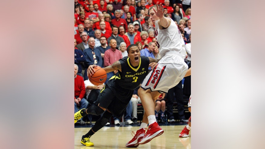 Oregon's Joseph Young (3) dribbles around the defense of Arizona's Kaleb Tarczewski during the first half of an NCAA college basketball game Thursday, Feb. 6, 2014, in Tucson, Ariz. (AP Photo/John MIller)