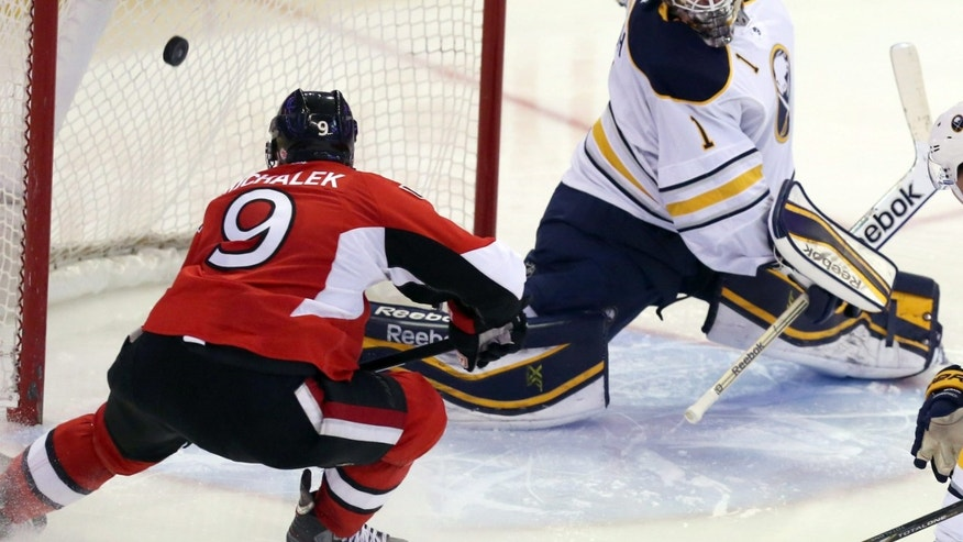 Ottawa Senators' Milan Michalek (9) scores on Buffalo Sabres goaltender Jhonas Enroth (1) during the third period of an NHL hockey game, Thursday, Feb. 6, 2014 in Ottawa, Ontario. Ottawa defeated Buffalo 3-2. (AP Photo/The Canadian Press, Fred Chartrand)