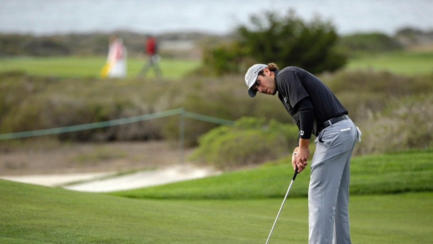 Andrew Loupe makes a birdie putt on the 14th green of the Monterey Peninsula Country Club Shore Course during the first round of the AT&T Pebble Beach Pro-Am golf tournament on Thursday, Feb. 6, 2014, in Pebble Beach, Calif. (AP Photo/Eric Risberg)