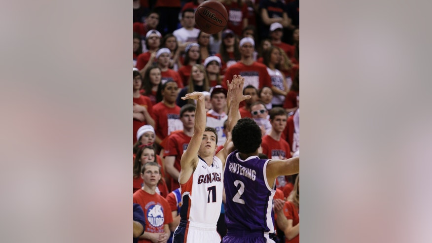 Gonzaga's David Stockton (11) attempts a jump shot against Portland's Alec Wintering (2) during the first half of an NCAA college basketball game, on Wednesday, Feb. 5, 2014, in Spokane, Wash. (AP Photo/Young Kwak)