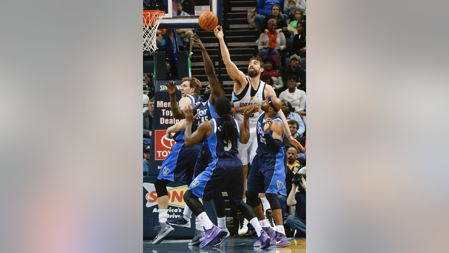 Memphis Grizzlies center Marc Gasol (33), of Spain, reaches for a rebound over Dallas Mavericks defenders Dirk Nowitzki, left, DeJuan Blair (45), Jae Crowder and Vince Carter (25) in the first half of an NBA basketball game, Wednesday, Feb. 5, 2014, in Memphis, Tenn. (AP Photo/Lance Murphey)