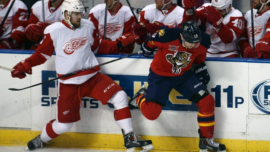 Detroit Red Wings' Riley Sheahan (15) and Florida Panthers' Scottie Upshall (19) battle for the puck during the first period of an NHL hockey game in Sunrise, Fla., Thursday, Feb. 6, 2014. (AP Photo/J Pat Carter)