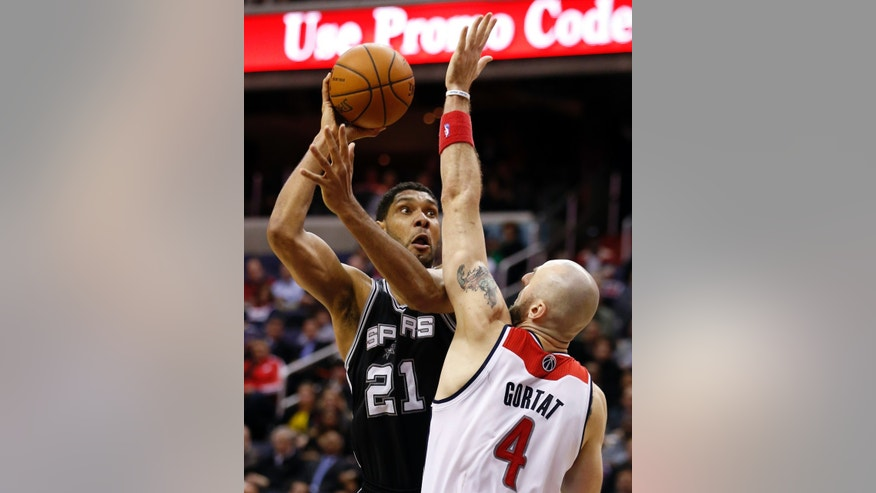 San Antonio Spurs forward Tim Duncan (21) shoots over Washington Wizards center Marcin Gortat (4), from Poland, in the first overtime of an NBA basketball game on Wednesday, Feb. 5, 2014, in Washington. Duncan had 31 points and the Spurs won 125-118 in double overtime. (AP Photo/Alex Brandon)