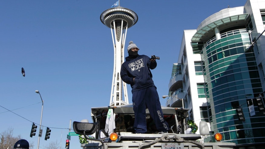 Seattle Seahawks' Marshawn Lynch stands on a military vehicle's hood during a parade for NFL football's Super Bowl XLVIII champions in Seattle, Wednesday, Feb. 5, 2014. The Seahawks defeated the Denver Broncos on Sunday. (AP Photo/John Froschauer)