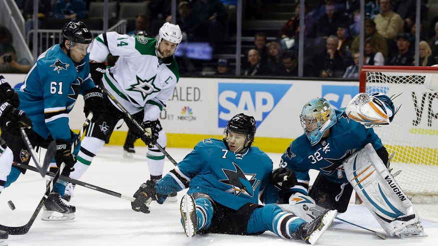 San Jose Sharks' Brad Stuart (7) falls down as he blocks a shot next to goalie Alex Stalock and defenseman Justin Braun (61) uring the second period of an NHL hockey game against the Dallas Stars on Wednesday, Feb. 5, 2014, in San Jose, Calif. (AP Photo/Marcio Jose Sanchez)