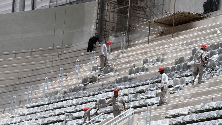 FILE - In this Jan. 21, 2014 file photo released by Portal da Copa, workers install seats at the Arena da Baixada stadium in Curitiba, Brazil. The southern city of Curitiba is expected to remain in the World Cup despite construction delays on its stadium, Brazilian Sports Minister Aldo Rebelo said Wednesday, Feb. 5, 2014. During a visit to the city, he expressed confidence that local organizers will be able to show FIFA that the stadium will be ready in time to hold its four matches scheduled for football's showcase event in June. (AP Photo/Portal da Copa, Paulino Menezes, File)