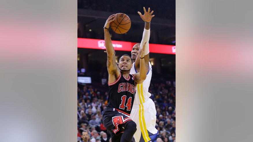 Chicago Bulls' D.J. Augustin (14) scores past Golden State Warriors' Marreese Speights during the first half of an NBA basketball game, Thursday, Feb. 6, 2014, in Oakland, Calif. (AP Photo/Marcio Jose Sanchez)