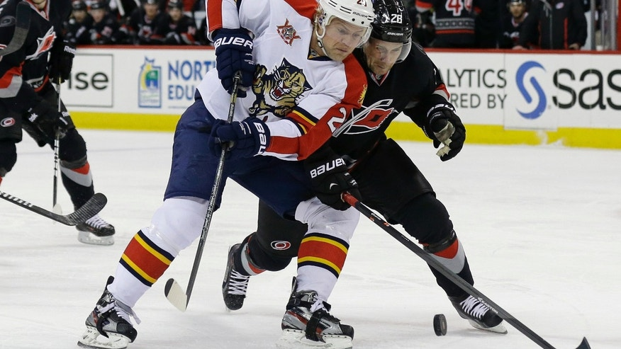 Carolina Hurricanes' John-Michael Liles, right, and Florida Panthers' Sean Bergenheim (20), of Finland, skate for the puck during the first period of an NHL hockey game in Raleigh, N.C., Friday, Feb. 7, 2014. (AP Photo/Gerry Broome)