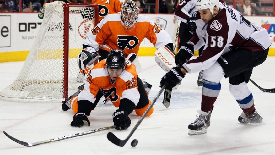 Philadelphia Flyers' Luke Schenn, left, and Colorado Avalanche' Patrick Bordeleau, right, reach for the loose puck while goalie Steve Mason looks on during the first period of an NHL hockey game, Thursday, Feb. 6, 2014, in Philadelphia. (AP Photo/Tom Mihalek)
