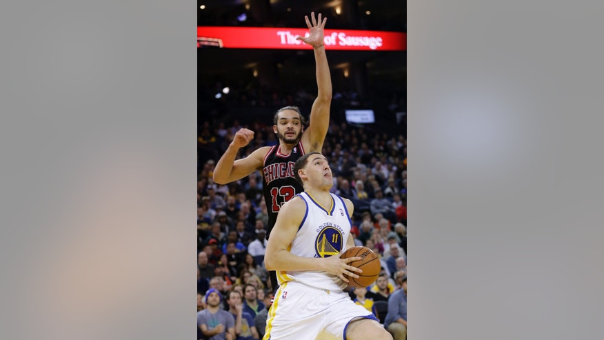 Golden State Warriors' Klay Thompson (11) drives past Chicago Bulls' Joakim Noah (13) during the second half of an NBA basketball game on Thursday, Feb. 6, 2014, in Oakland, Calif. Golden State won 102-87. (AP Photo/Marcio Jose Sanchez)