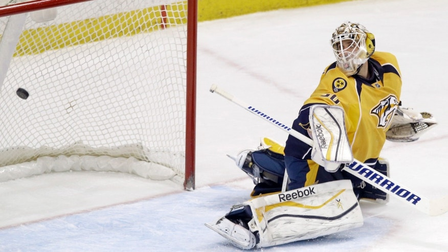 Nashville Predators goalie Carter Hutton gives up the winning goal in overtime of an NHL hockey game to Minnesota Wild's Nino Niederreiter of Switzerland, Thursday, Feb. 6, 2014, in St. Paul, Minn. The Wild won 3-2.  (AP Photo/Jim Mone)