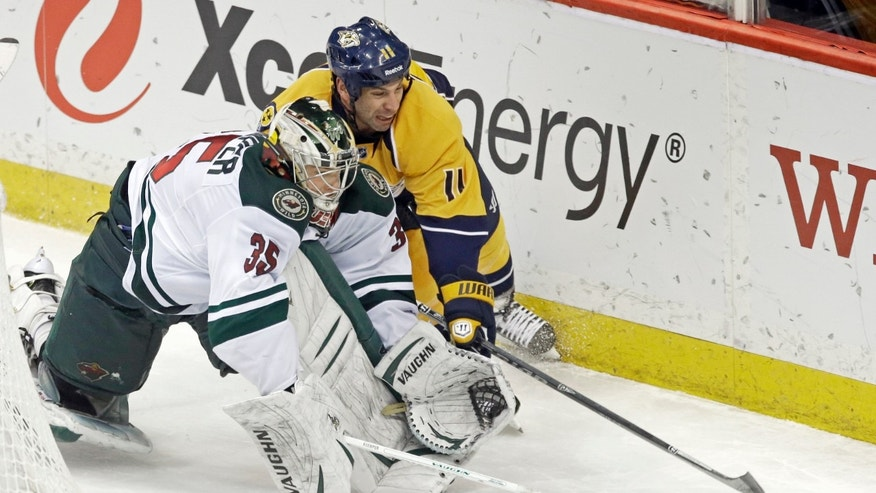 Minnesota Wild goalie Darcy Kuemper, left, stepped away from the net to keep the puck away from Nashville Predators' David Legwand in the third period of an NHL hockey game, Thursday, Feb. 6, 2014, in St. Paul, Minn. The Wild won 3-2 in overtime. (AP Photo/Jim Mone)