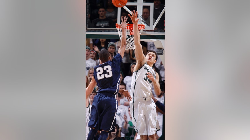 Michigan State's Gavin Schilling, right, defends on a shot by Penn State's Tim Frazier (23) during the second half of an NCAA college basketball game, Thursday, Feb. 6, 2014, in East Lansing, Mich. Michigan State won 82-67. (AP Photo/Al Goldis)