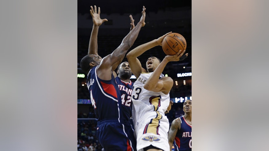 New Orleans Pelicans power forward Anthony Davis (23) shoots against Atlanta Hawks power forward Paul Millsap (4) and power forward Elton Brand (42) in the second half of an NBA basketball game in New Orleans, Wednesday, Feb. 5, 2014. The Pelicans won 105-100. (AP Photo/Gerald Herbert)