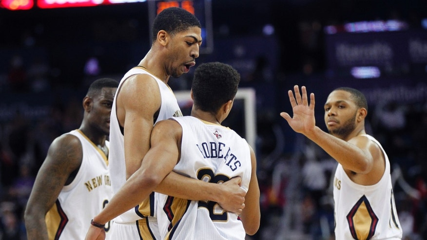 New Orleans Pelicans point guard Brian Roberts (22) is congratulated by power forward Anthony Davis, center, shooting guard Eric Gordon, right, and shooting guard Anthony Morrow, left, after scoring a key basket in the final moments of the second half of an NBA basketball game against the Atlanta Hawks in New Orleans, Wednesday, Feb. 5, 2014. The Pelicans won 105-100.  (AP Photo/Gerald Herbert)
