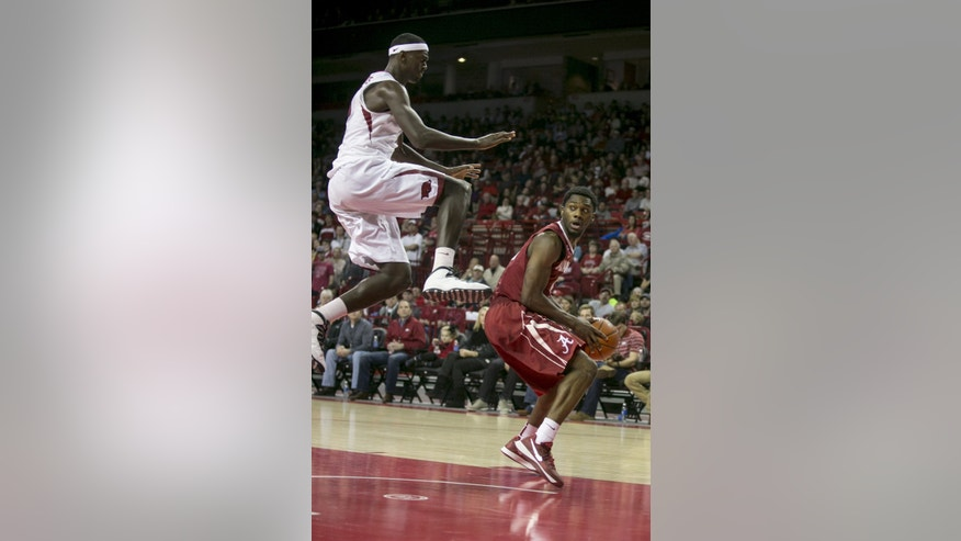 Alabama guard Algie Key, right,looks to drive to the basket as Arkansas forward Bobby Portis attempts to contest his shot during the second half of an NCAA college basketball game on Wednesday, Feb. 5, 2014, in Fayetteville, Ark. Arkansas defeated Alabama 65-58. (AP Photo/Gareth Patterson)