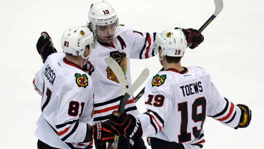 Chicago Blackhawks left winger Patrick Sharp (10) and right winger Marian Hossa (81), of the Czech Republic, celebrate a goal by center Jonathan Toews (19) against the Anaheim Ducks in the third period of an NHL hockey game in Anaheim, Calif., Wednesday, Feb. 5, 2014. The Blackhawks won, 2-0. (AP Photo/Reed Saxon)