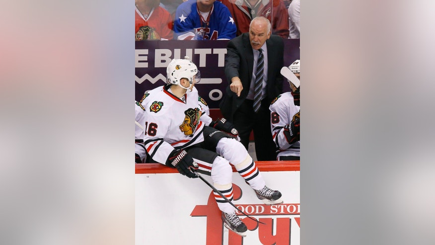 Chicago Blackhawks' Joel Quenneville shouts instructions to his players, including Marcus Kruger (16), of Sweden, during the second period in an NHL hockey game against the Phoenix Coyotes, Friday Feb. 7, 2014, in Glendale, Ariz. (AP Photo/Ross D. Franklin)