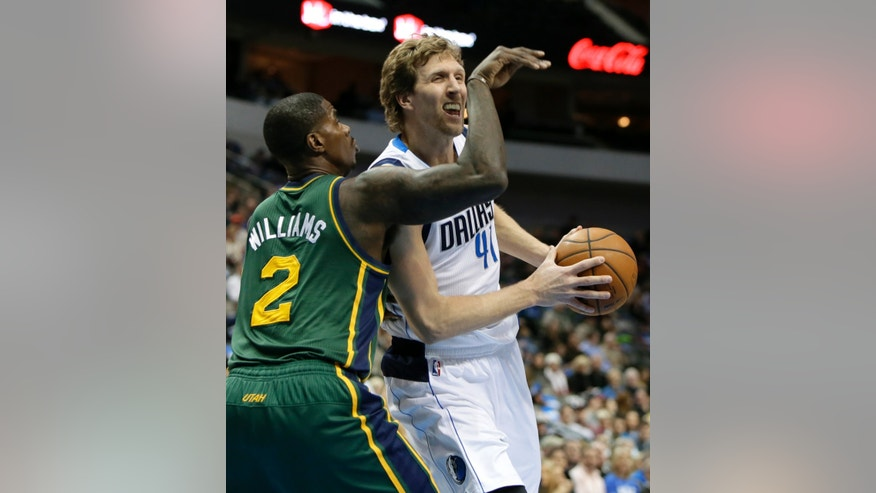 Dallas Mavericks forward Dirk Nowitzki, right, drives to the basket as Utah Jazz's Marvin Williams (2) defends in the first half of an NBA basketball game, Friday, Feb. 7, 2014, in Dallas. (AP Photo/Tony Gutierrez)