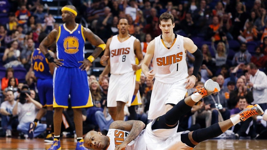 Phoenix Suns' P.J. Tucker, front, falls to the court after sinking a jump shot while being fouled by Golden State Warriors' Jermaine O'Neal (7) as Suns' Goran Dragic (1), of Slovenia, and Channing Frye (8) run over to Tucker during the first half of an NBA basketball game Saturday, Feb. 8, 2014, in Phoenix. (AP Photo/Ross D. Franklin)