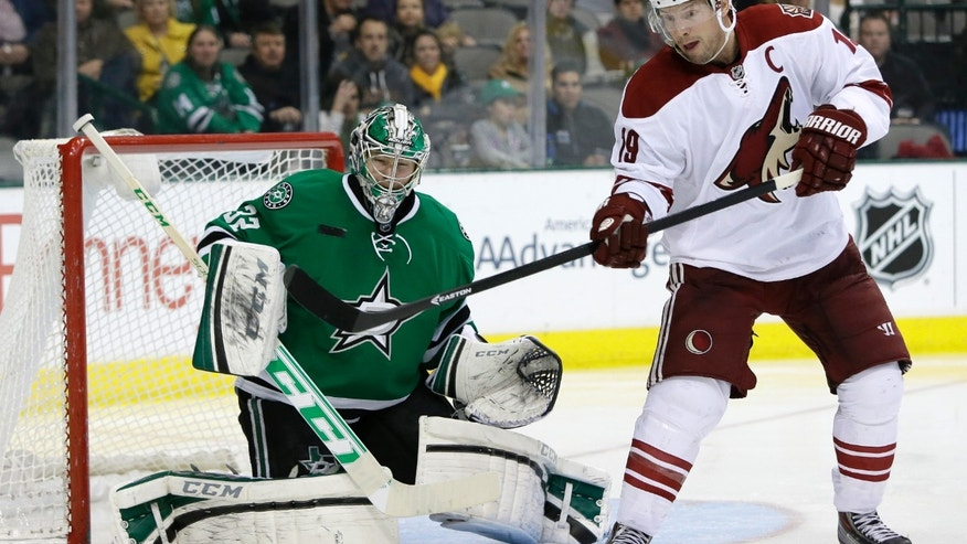 Phoenix Coyotes right wing Shane Doan (19) deflects the angle of a shot that Dallas Stars' Kari Lehtonen (32) stopped in the second period of an NHL hockey game, Saturday, Feb. 8, 2014, in Dallas. (AP Photo/Tony Gutierrez)