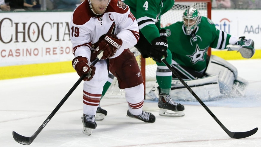 Phoenix Coyotes' Shane Doan (19) moves the puck towards the net as Phoenix Coyotes' Zbynek Michalek (4) helps goalie Kari Lehtonen (32) defend in the second period of an NHL hockey game, Saturday, Feb. 8, 2014, in Dallas. (AP Photo/Tony Gutierrez)