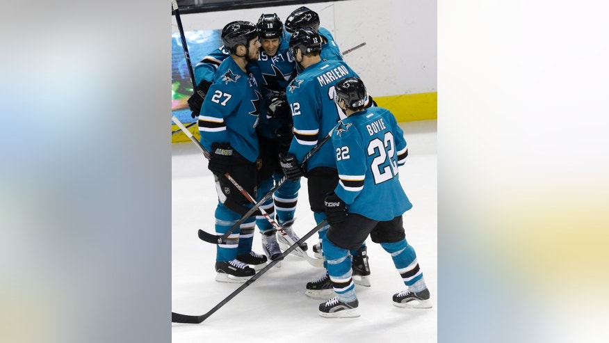 San Jose Sharks' Scott Hannan (27) is hugged by teammates after his goal against the Columbus Blue Jackets during the first period of an NHL hockey game, Friday, Feb. 7, 2014, in San Jose, Calif. (AP Photo/Marcio Jose Sanchez)