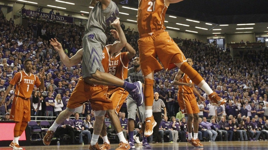 Texas forward Connor Lammert (21) defends as Kansas State guard/forward Wesley Iwundu shoots during an NCAA college basketball game Saturday, Feb. 8, 2014, in Manhattan, Kan. (AP Photo/The Wichita Eagle, Bo Rader) LOCAL TV OUT; MAGS OUT; LOCAL RADIO OUT; LOCAL INTERNET OUT