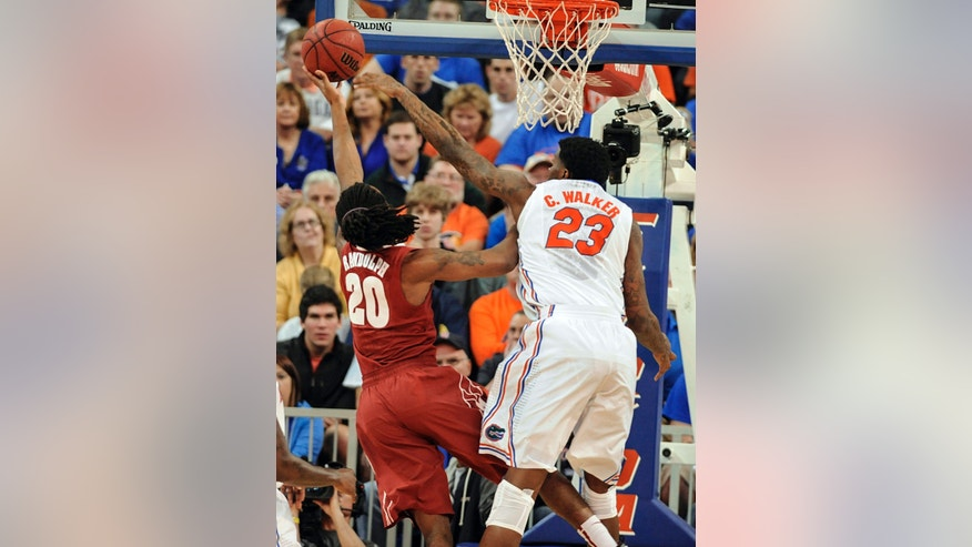 Florida's Chris Walker (23) tries to blocks shot by Alabama guard Levi Randolph (20) but fails during the first half of an NCAA college basketball game Saturday, Feb. 8, 2014, in Gainesville, Fla. (photo by Phil Sandlin)