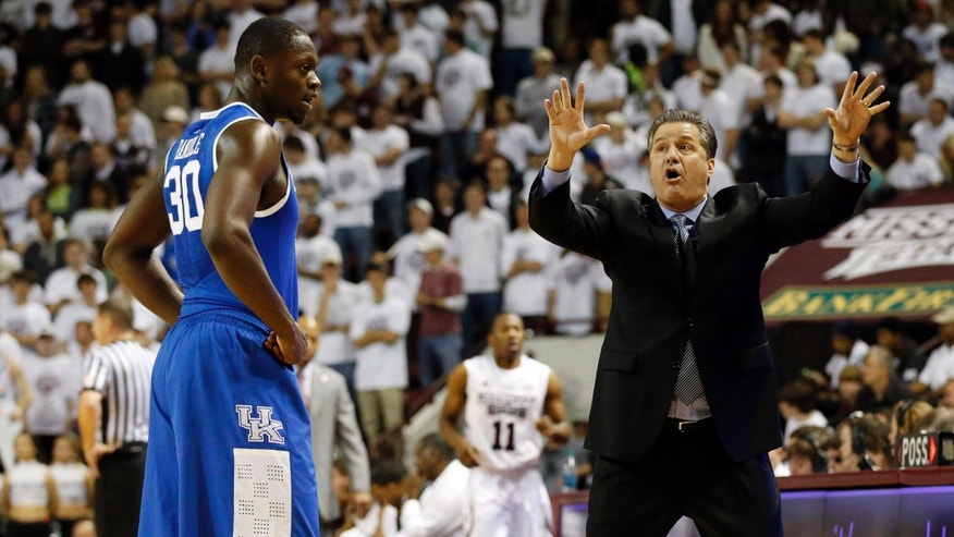Kentucky basketball coach John Calipari demonstrates a form of defense to forward Julius Randle (30) in the first half of an NCAA college basketball game against Mississippi State in Starkville, Miss., Saturday, Feb. 8, 2014. (AP Photo/Rogelio V. Solis)