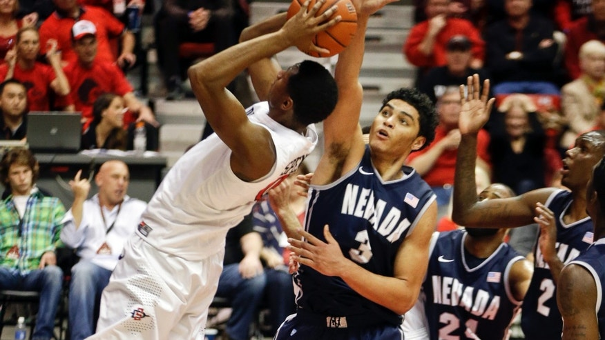 San Diego State's Skylar Spencer, left, has his shot blocked by Nevada forward AJ West during the first half of an NCAA college basketball game Saturday, Feb. 8, 2014, in San Diego. (AP Photo/Lenny Ignelzi)