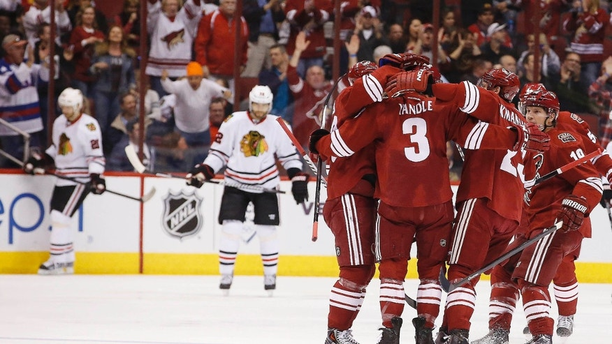 Phoenix Coyotes' Keith Yandle (3) celebrates his goal against the Chicago Blackhawks with teammates Oliver Ekman-Larsson, second from right, Shane Doan, right, and Mikkel Boedker, left, during the first period in an NHL hockey game, Friday Feb. 7, 2014, in Glendale, Ariz. (AP Photo/Ross D. Franklin)