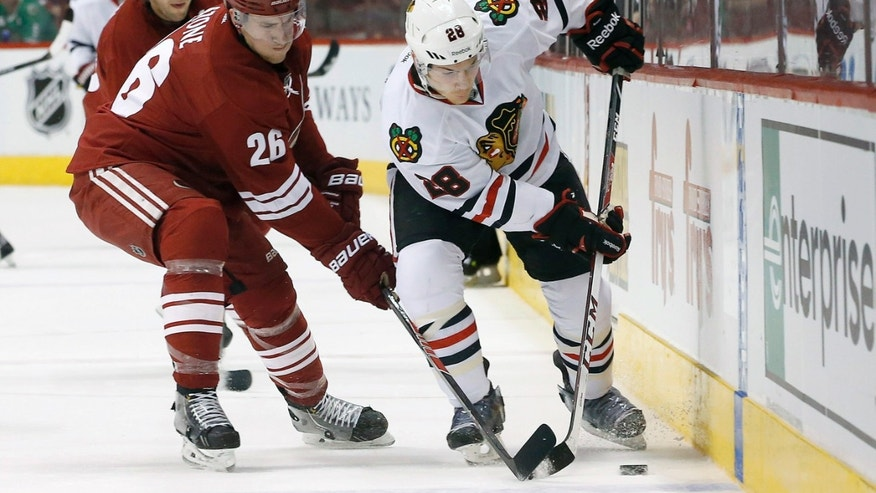 Chicago Blackhawks' Ben Smith (28) battles with Phoenix Coyotes' Michael Stone (26) for control of the puck during the first period in an NHL hockey game, Friday Feb. 7, 2014, in Glendale, Ariz. (AP Photo/Ross D. Franklin)