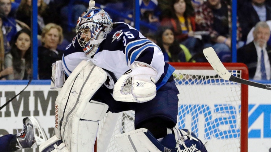 Winnipeg Jets goalie Al Montoya leaps into the air to avoid a sliding St. Louis Blues player during the second period of an NHL hockey game Saturday, Feb. 8, 2014, in St. Louis. (AP Photo/Jeff Roberson)