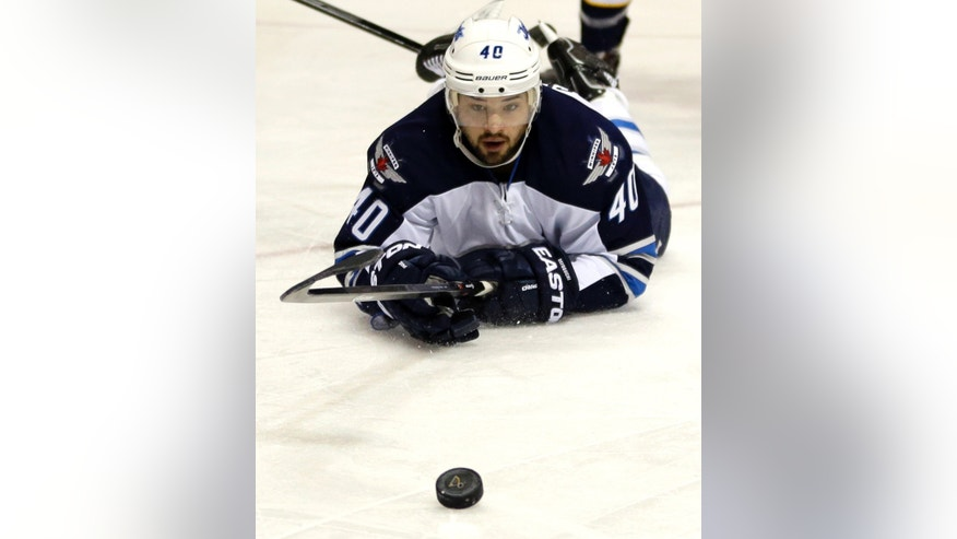 Winnipeg Jets' Devin Setoguchi keeps his eye on the puck after falling to the ice during the first period of an NHL hockey game against the St. Louis Blues Saturday, Feb. 8, 2014, in St. Louis. (AP Photo/Jeff Roberson)